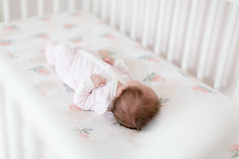 newborn baby girl sleeps in her neutral white crib