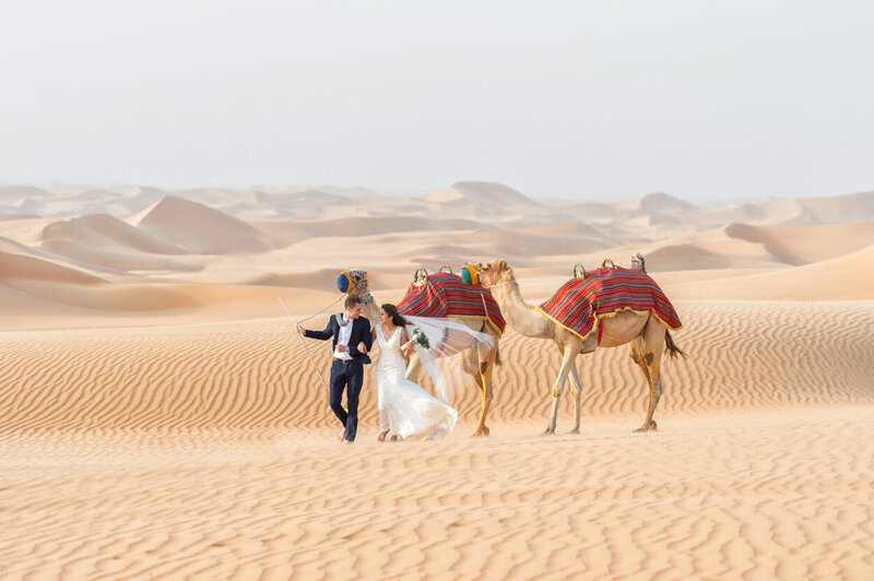 Dubai wedding photoshoot amidst desert dunes with camels organized by Lovely & Planned