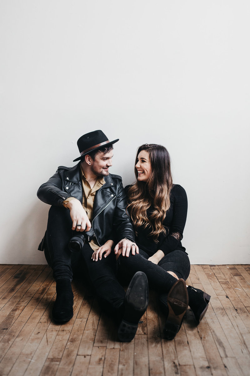 A+C-brandshoot-19-WEB-seattle-washington-wedding-photographers-white-wall-hat-desk-layout-laugh-candid-couple-goals-cute-work-together-business-camera-canon-guy-ring-black-leather-jacket-skinny-jeans-golden-hair-wood