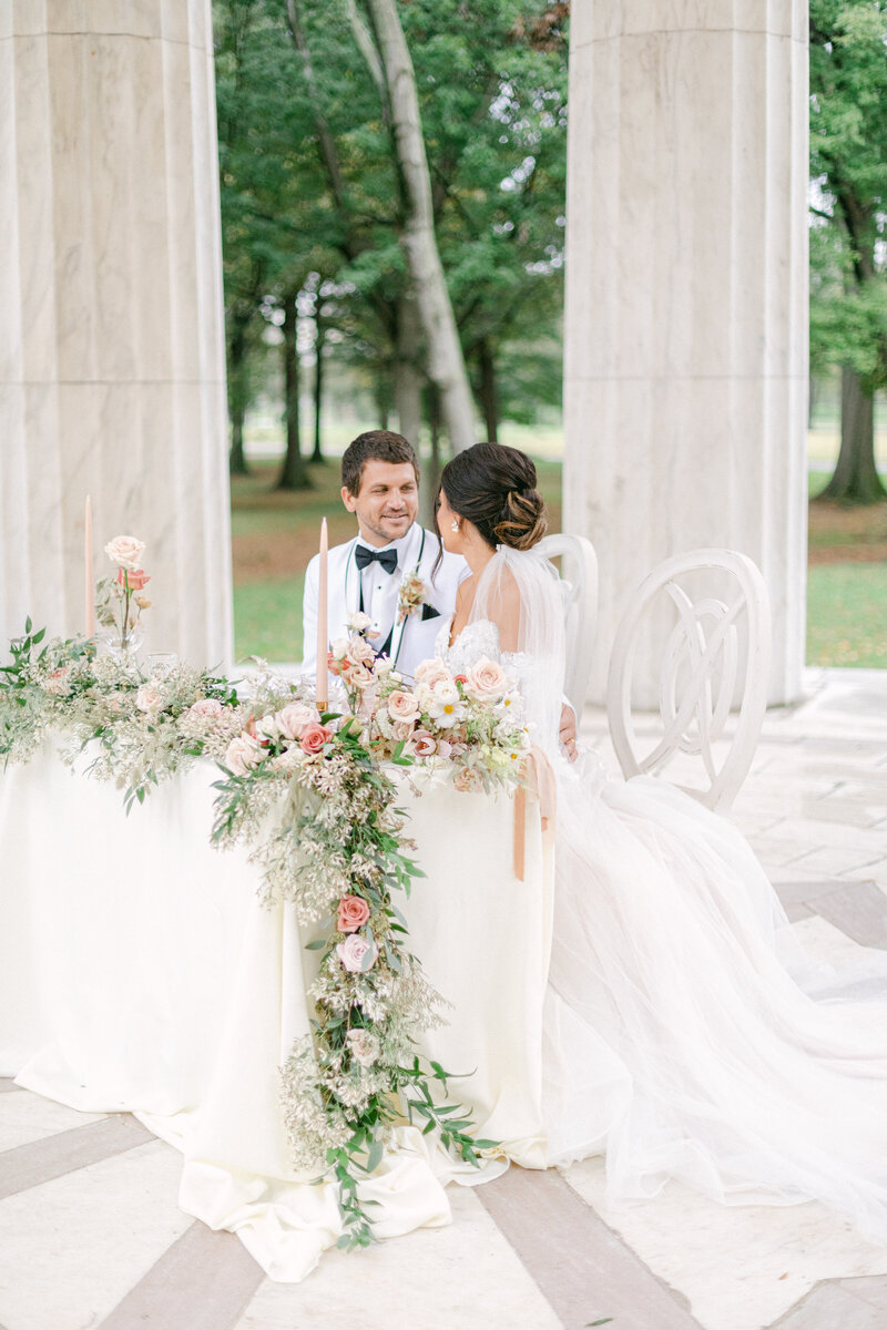 bride and groom sitting at sweetheart table at Washington DC Romantic Classic Wedding at the Lincoln Memorial by Costola Photography