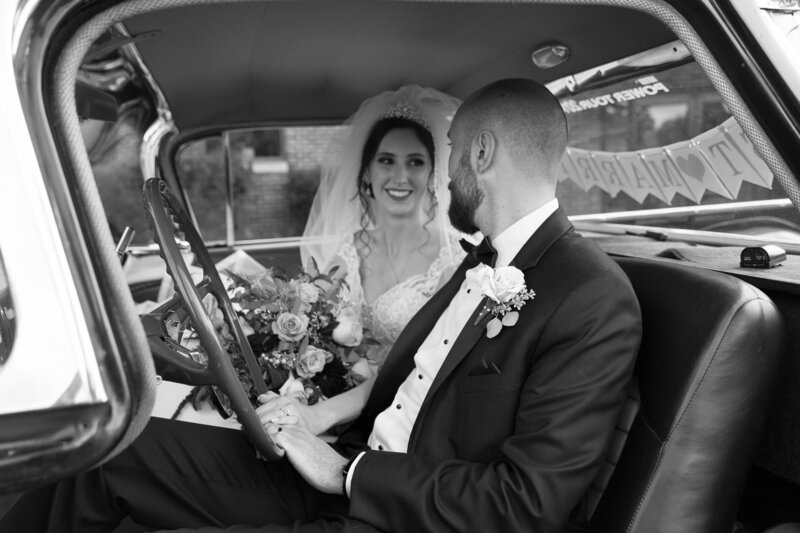 bride and groom inside of vintage car on wedding day in port huron