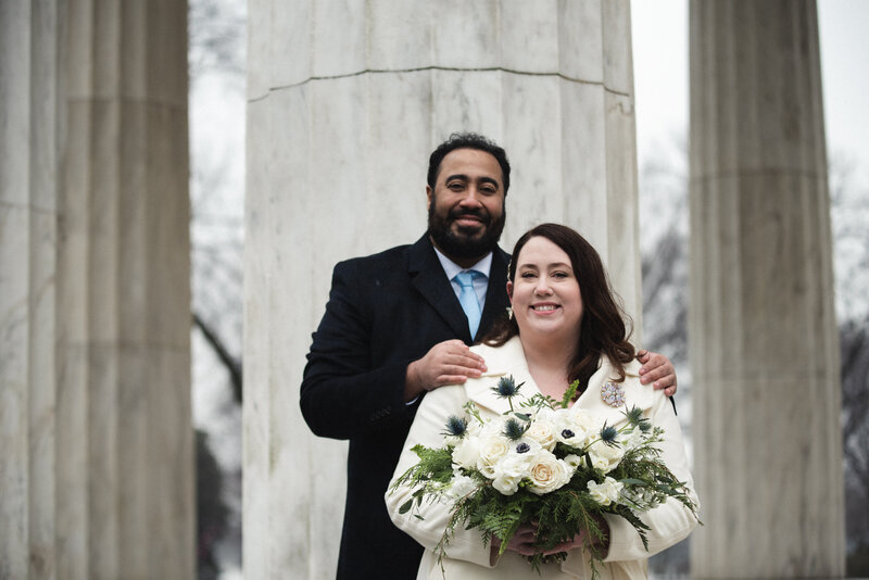 Bridal bouquet and groom in front of War Memorial in Washington, DC