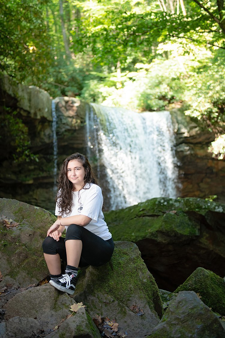 Grunge high school senior girl seated on rocks in front of Cucumber Falls at OhioPyle State Park in PA