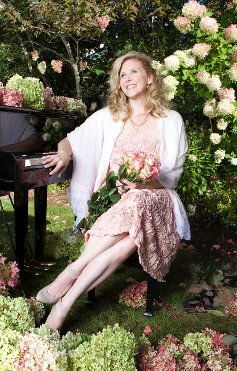 Branding portrait of Author Linda Brooks sitting on piano bench next to grand piano placed in her garden holding bouquet of roses in her lap