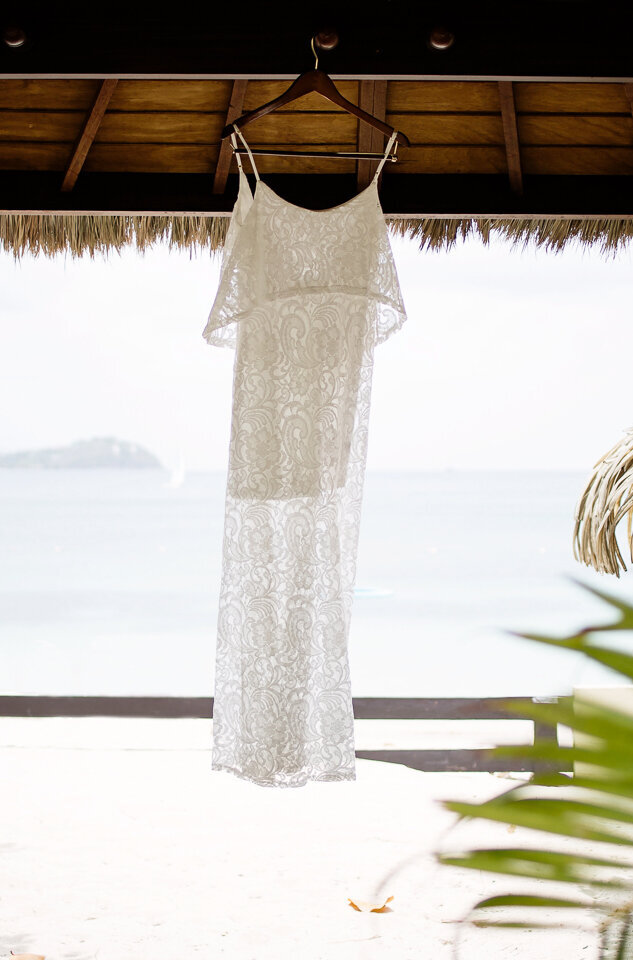 A bride's wedding dress hanging in the cabana at Sandals Grande wedding venue in St Lucia.