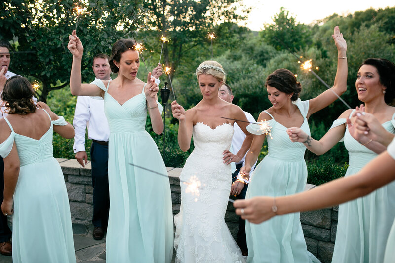 Bride celebrates with her bridal party with sparklers at her wedding reception