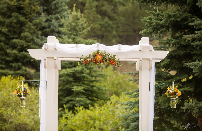 Detail of the white wood wedding arbor with orange florals at Mountain View Ranch