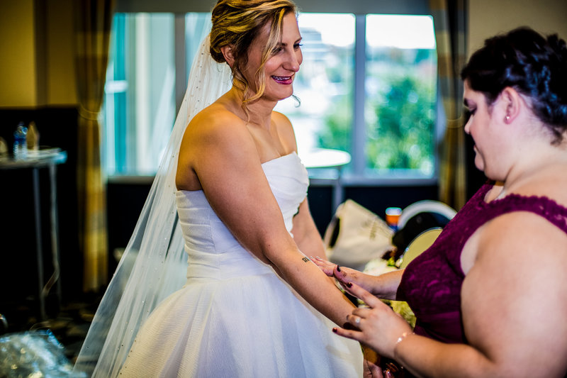 Maid of Honor helping bride on wedding day
