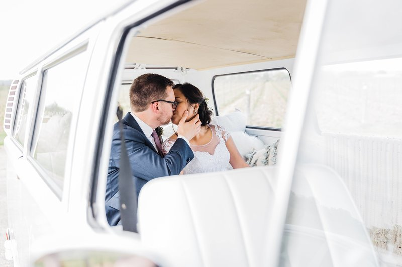 Bride and groom share a kiss in the back of their Kombi van wedding car from Long Weekend Bus