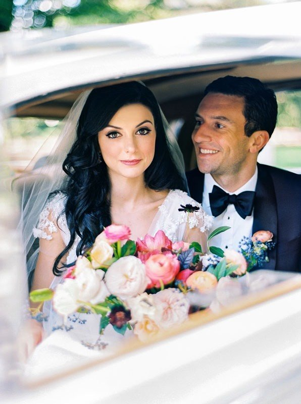 bride and groom with bouquet in car