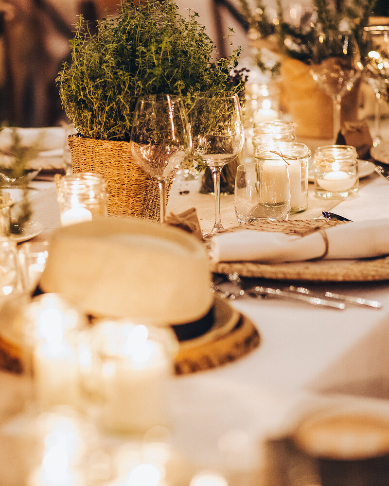 A rustic wedding table set up with herbs in pots for an elegant outdoor wedding.