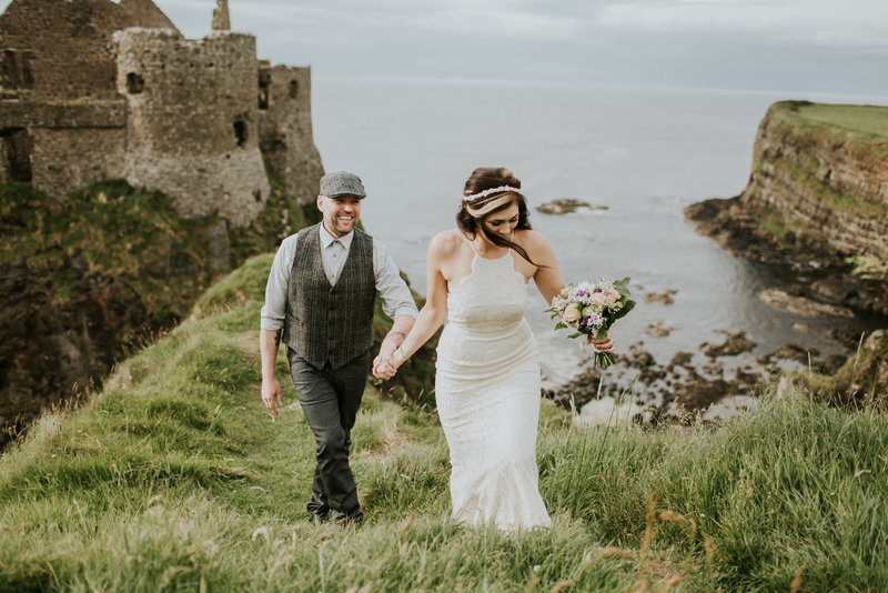 Dunluce Castle Northern Ireland Elopement Couple Holding Hands on Cliff