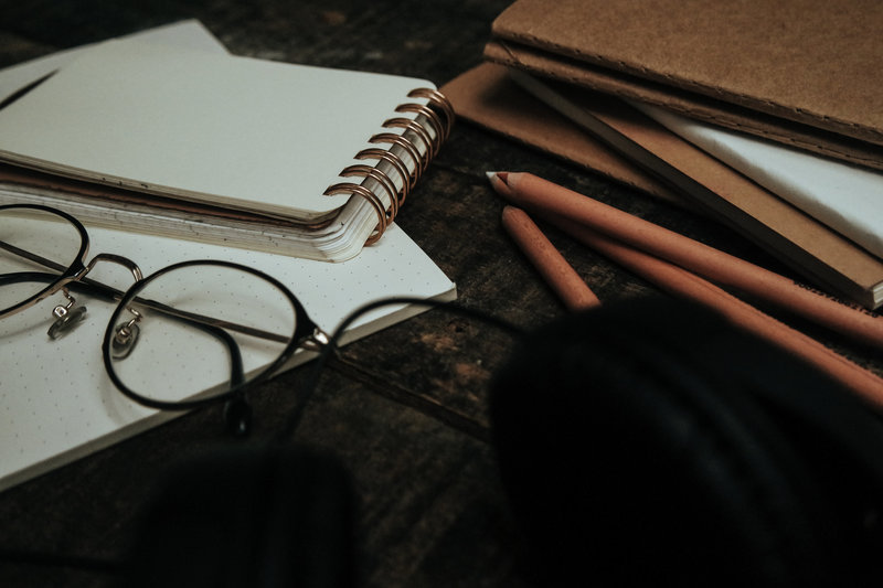Glasses, notebooks and pencils on a desk