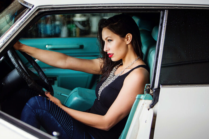 model  with red lipstick in vintage cadillac