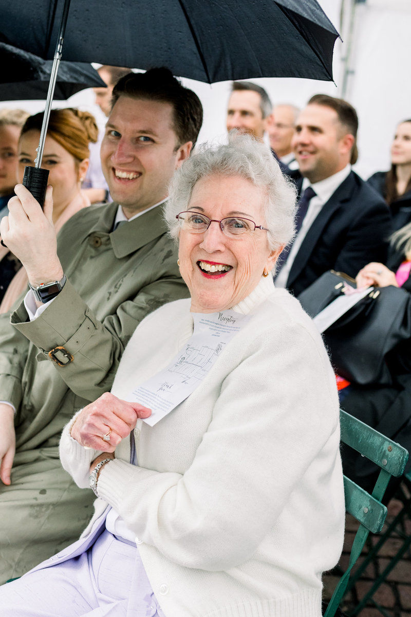 A grandmother laughs in the middle of a wedding ceremony as rain pours down on the guests