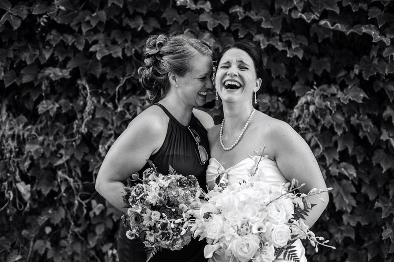Erie, PA bride laughs uncontrollably with one of her bridesmaids
