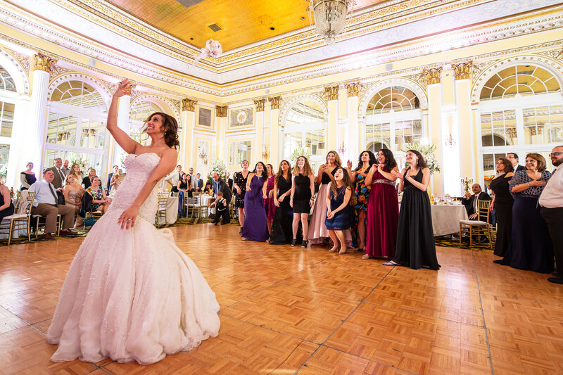 Bride tossing a bouquet at a wedding and flowers are still in the air in a luxury banquet hall.