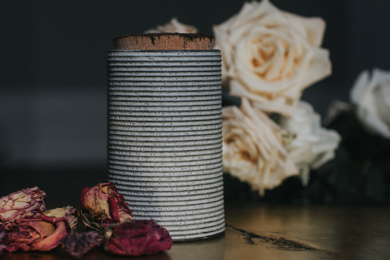 Handmade ceramic urn with rustic gray ring design and raw cork lid surrounded by red and white roses.