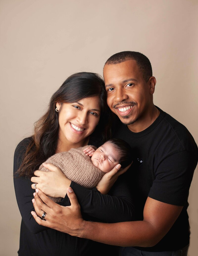 newborn family dressed in black in studio with baby wrap in brown