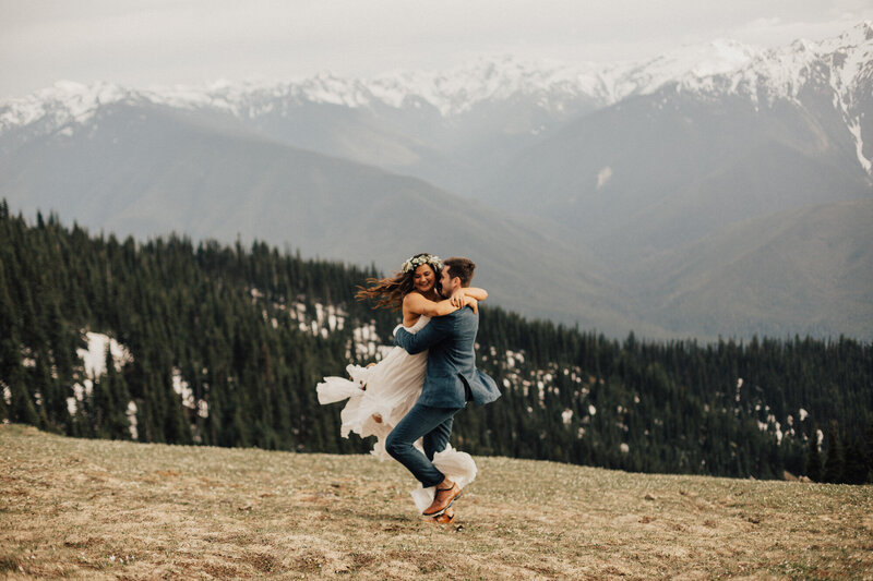 bride and groom holding each other on mountain top