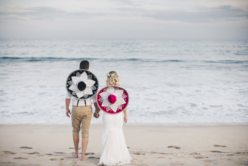 Bride and Groom standing on the beach wearing sombreros