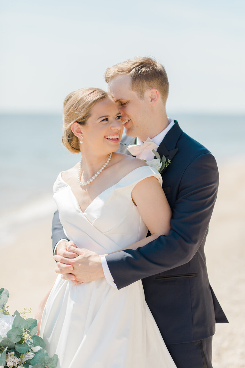 couple standing on beach at Inn at Perry Cabin wedding in St Michaels Maryland by Costola Photography