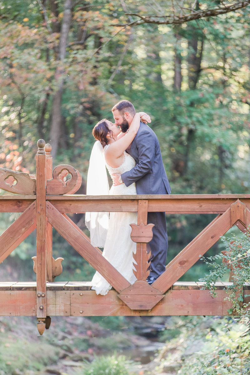 Bride and groom embrace on a bridge while kissing on their wedding day
