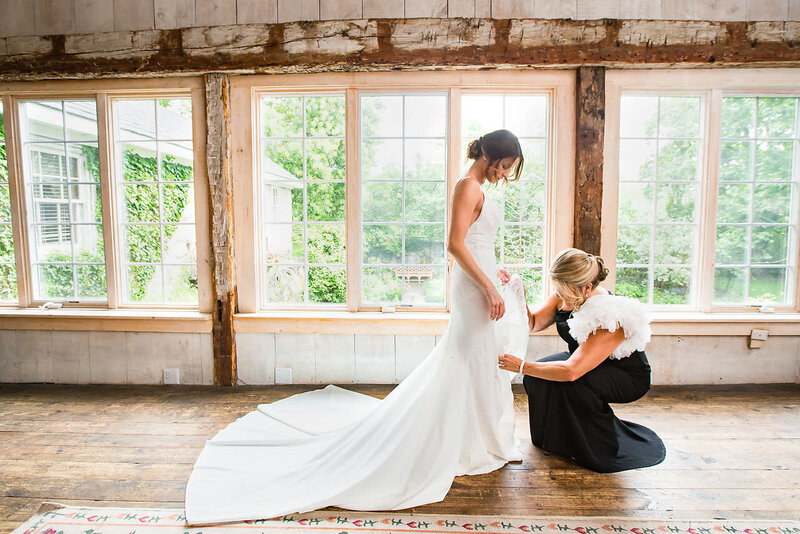 Mother of bride helps her daughter get dressed on her wedding day