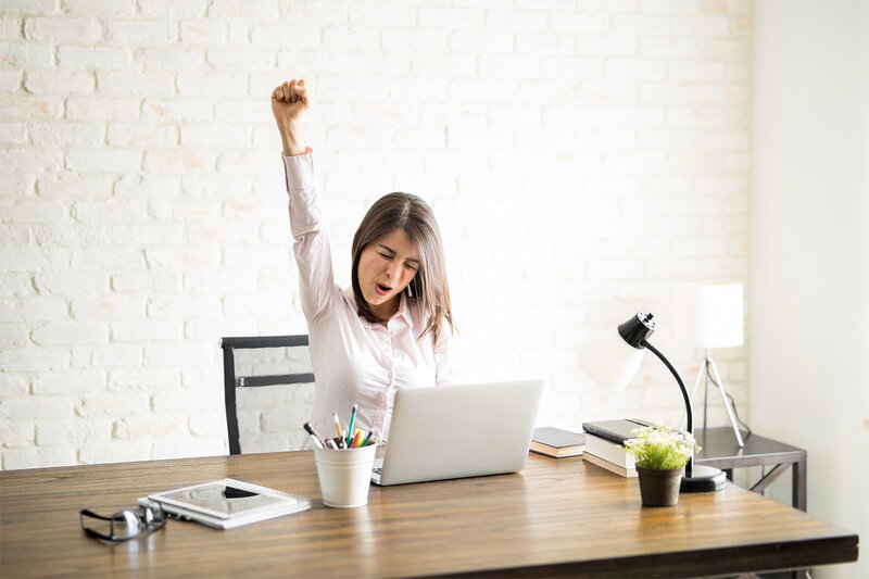 woman with white brick wall  at desk excited and smiling with hand in air