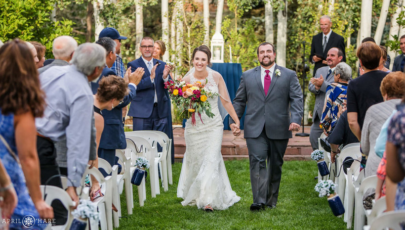 Bride and Groom walk hand in hand down aisle at ourdoor wedding ceremony at Church Ranch Event Center in Westminster Colorado