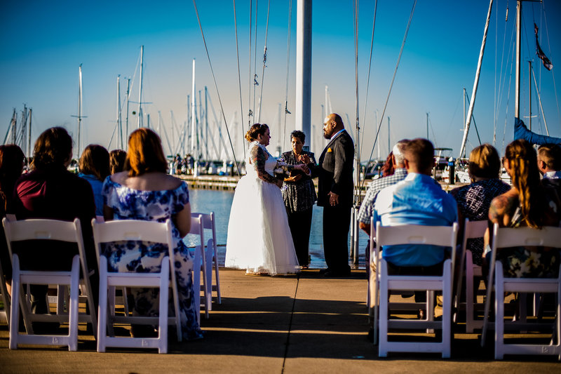 Couple exchanges vows in front of the flagpole at the Erie Yacht Club