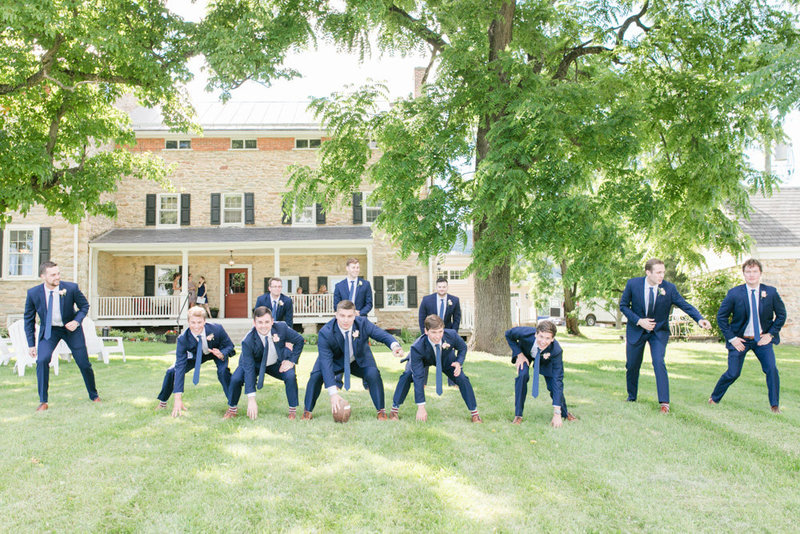 groomsmen playing football outside of inn at springfield manor winery and distillery wedding by costola photography