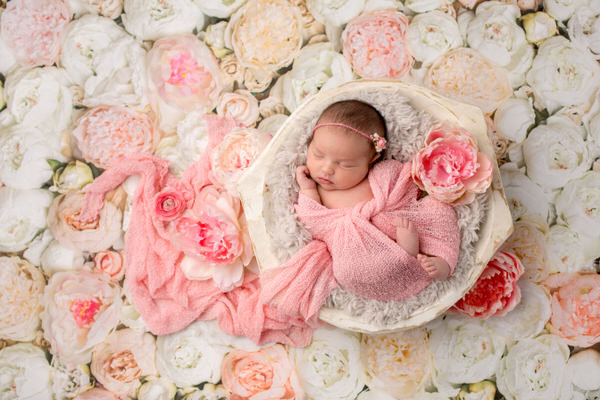 Newborn girl swaddled in pink on a floral background