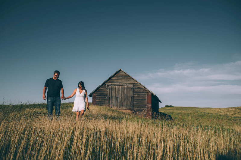 couple walks in field of tall grass with barn in background