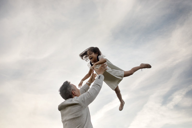 candid image of a father tossing his laughing daughter in the air