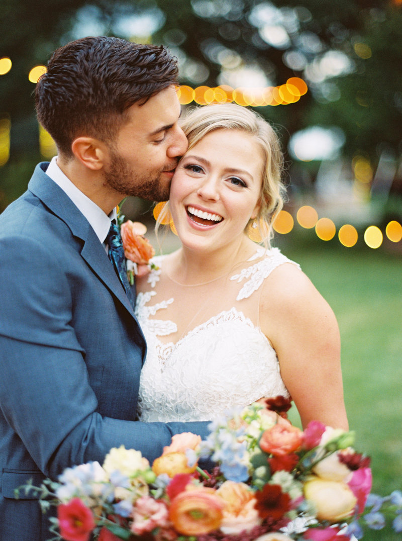 Groom kisses smiling bride on cheek