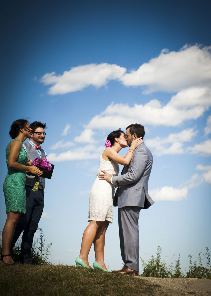 Bride & groom kiss on a beautiful day in Portland, Maine as bridesmaid & groomsman look on