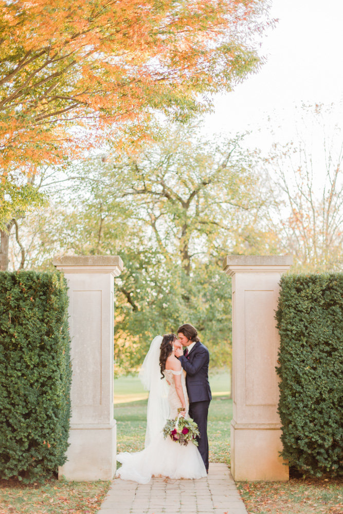 couple kissing outside of manor at great marsh estate wedding in northern virginia by costola photography