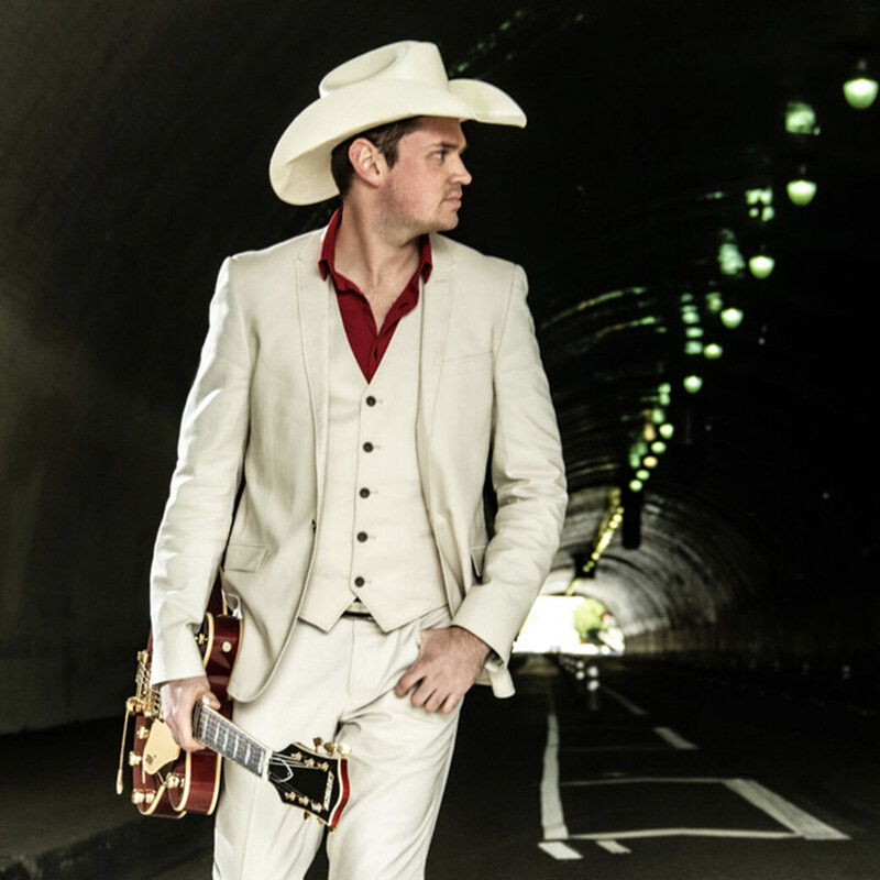 Country Music Portrait Los Angeles Ben Klick standing in tunnel wearing white suit red shirt white cowboy hat green lights on roof of tunnel beside him