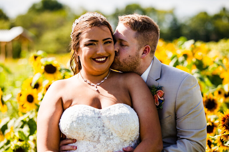 Groom kisses bride's cheek in sunflower field at Port Farms