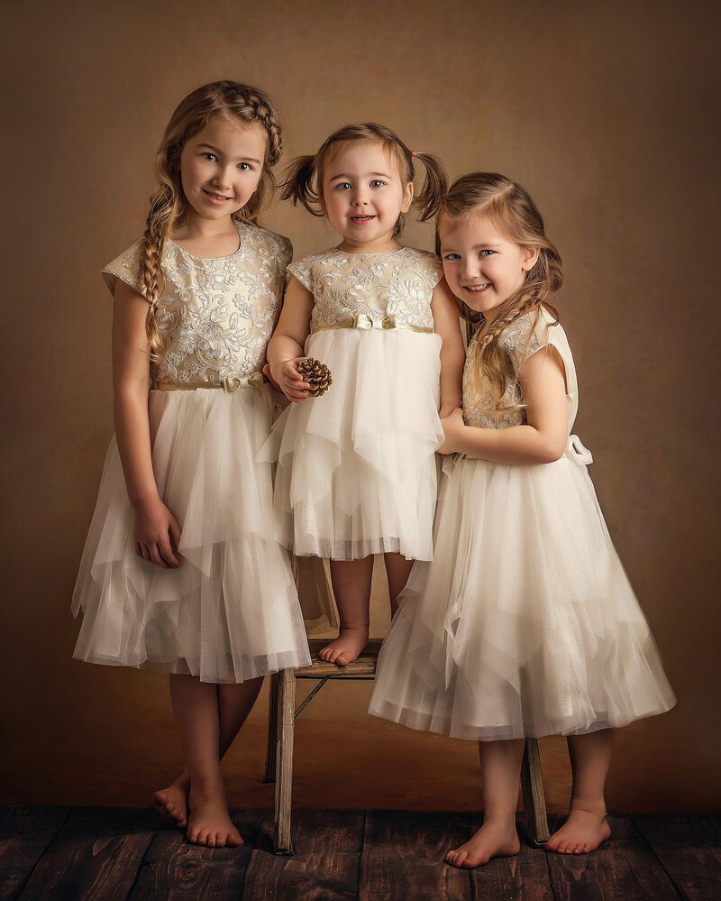 3 sisters in ivory dresses smile in fine art portrait session