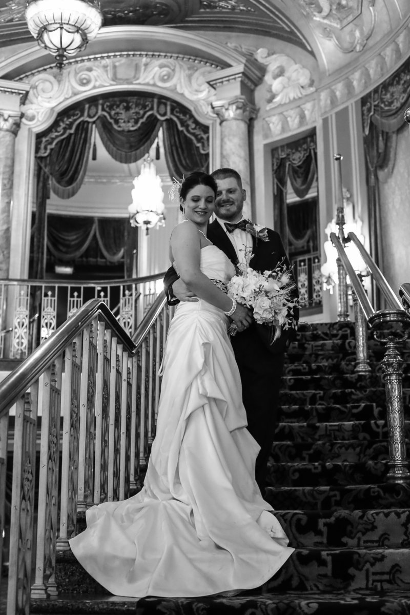 Bride and groom stand on grand staircase at their Warner Theater wedding in Erie, PA