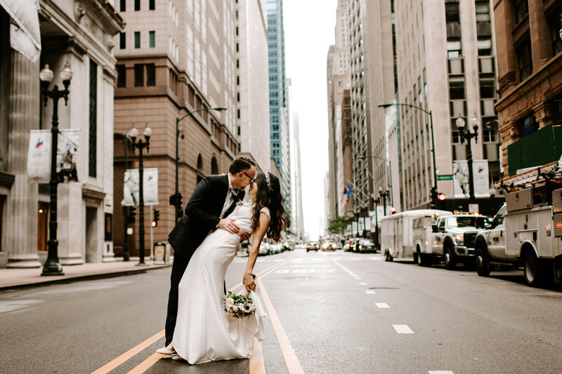 bride and groom standing in city street kissing