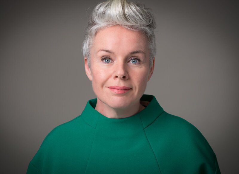 portrait of a woman with short grey hair and green top in front of grey background