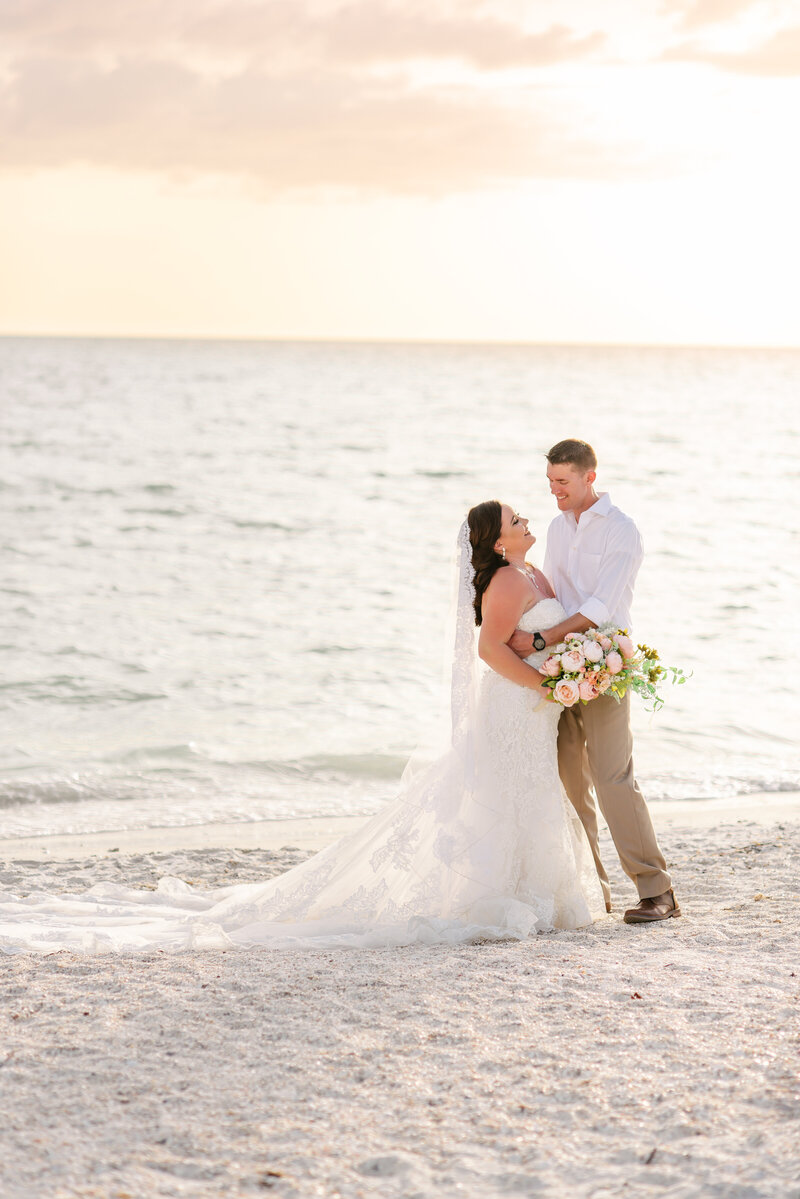 A bride and groom pose on the beach after their outdoor Florida wedding.