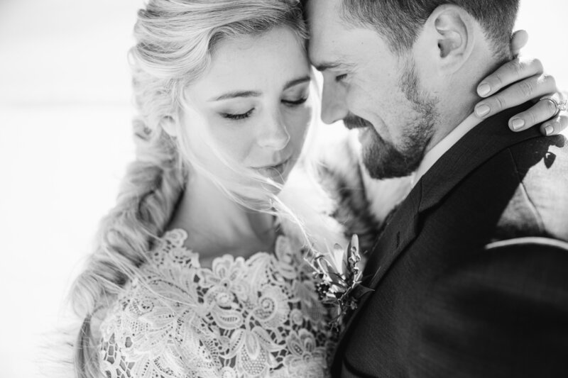 bride and groom with their heads together and embracing in a black and white photo