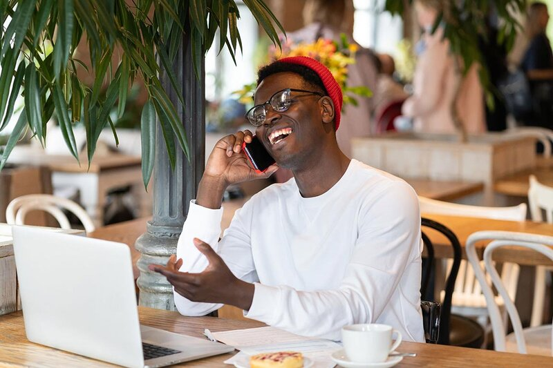 Millenial talking on phone in front of computer to illustrate how to get high-paying clients on Upwork