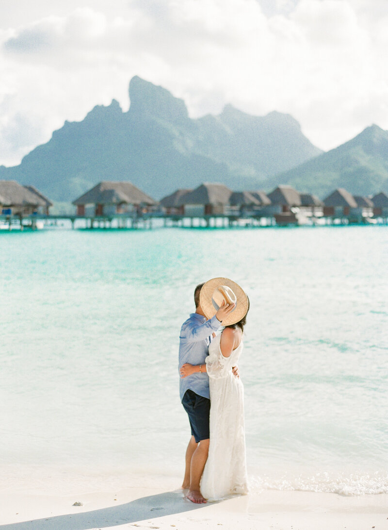 Couple kissing hidden hat beach photo session overwater bungalow blue lagoon at sunset