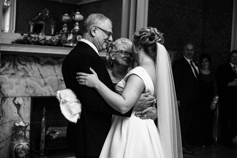 MOther and father hug their daughter on her wedding day the Watson Curtze Museum in Erie, PA