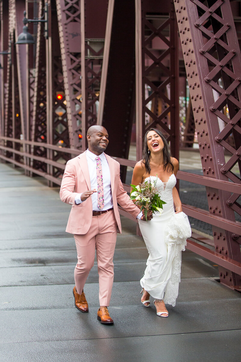 Bride and groom laughing at a Chicago river bridge.